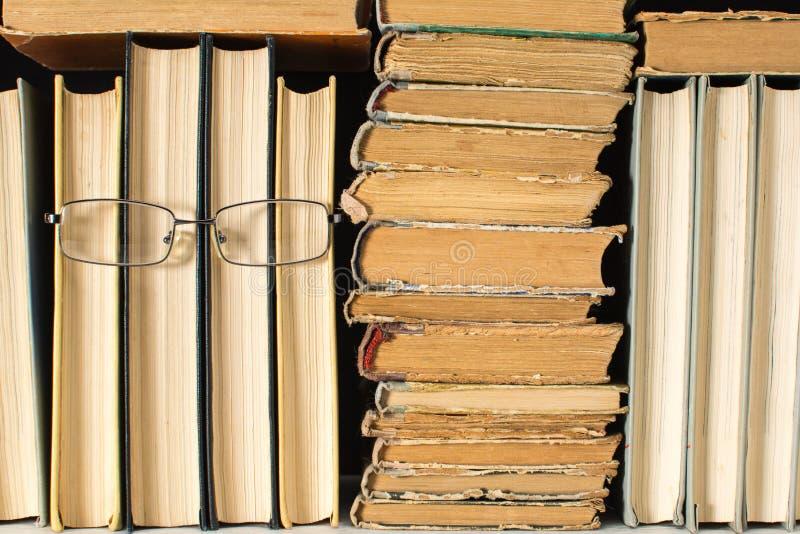 Boekenrek met een antropoide gezicht van sommige boeken in glazen met een bos van oude sjofele boeken Het concept lezing stock fotografie