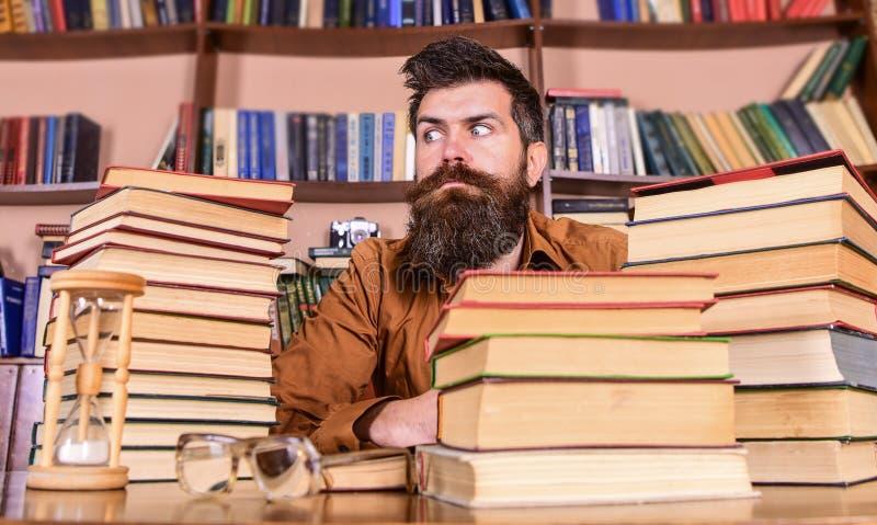 Boekenwurmconcept De mens op strikt gezicht zit tussen stapels van boeken, terwijl het bestuderen in bibliotheek, boekenrekken op royalty-vrije stock afbeelding