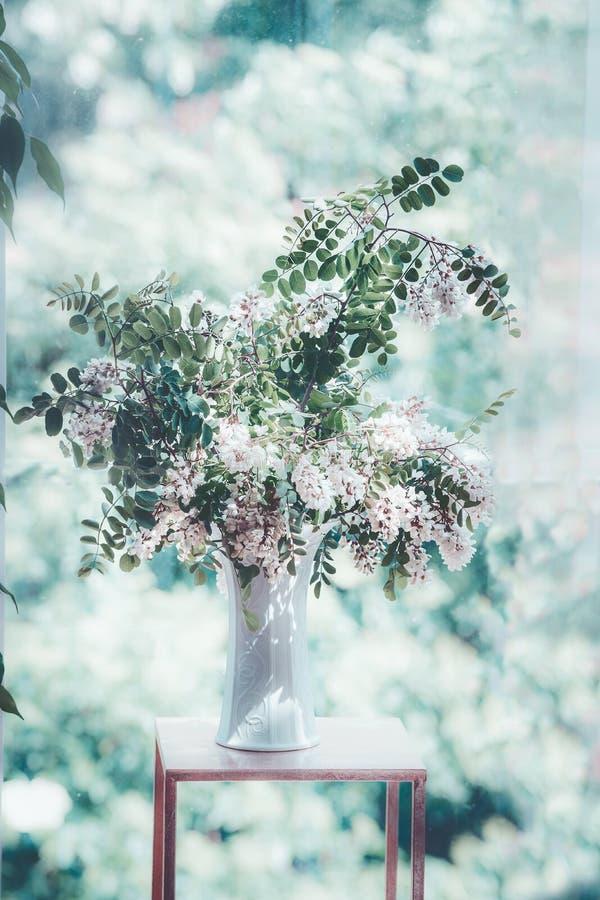 Boeket met bloeiende takken in vaas bij venster Comfortabel huisbinnenland stock foto