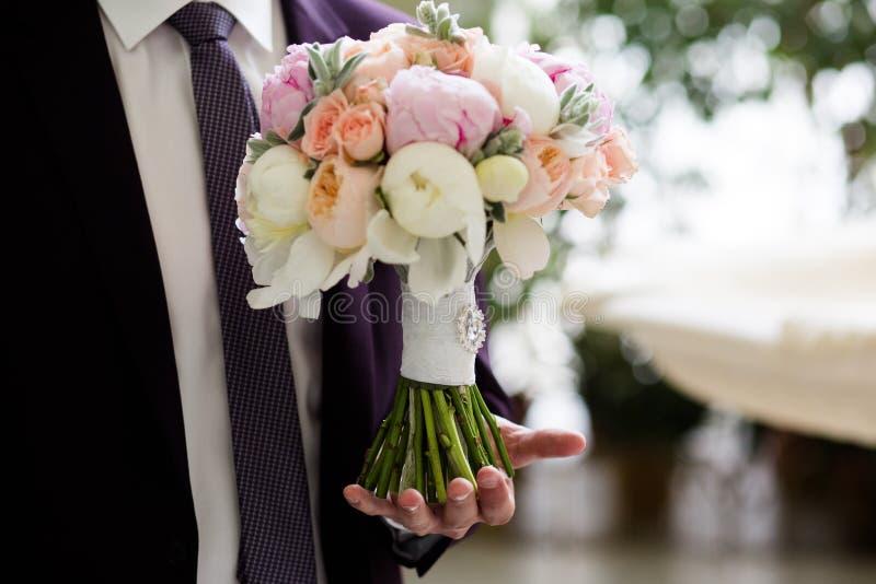 Boeket van bloemen in de handen van de bruidegom stock afbeeldingen