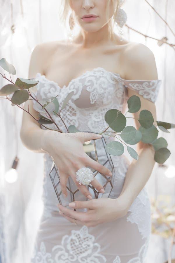 Boeket van bloemen in een vaas die een meisjesbruid in een elegante witte huwelijkskleding houden met een grote ring op zijn ving royalty-vrije stock fotografie