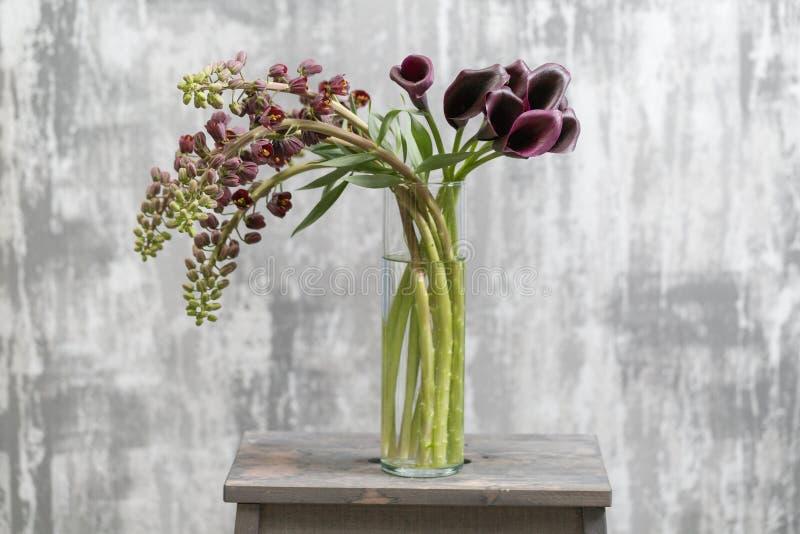 Boeket van de Mooie violet-bruine bloemen en Calla van Fritillaria De lentebloemen in vaas op houten lijst behang stock afbeelding