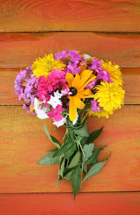 Boeket van de zomerbloemen op kleurrijke houten raad stock fotografie