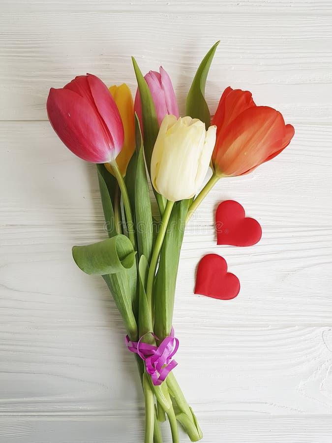 boeket van gekleurde witte houten achtergrond twee van de tulpenvalentijnskaart rode harten royalty-vrije stock afbeelding
