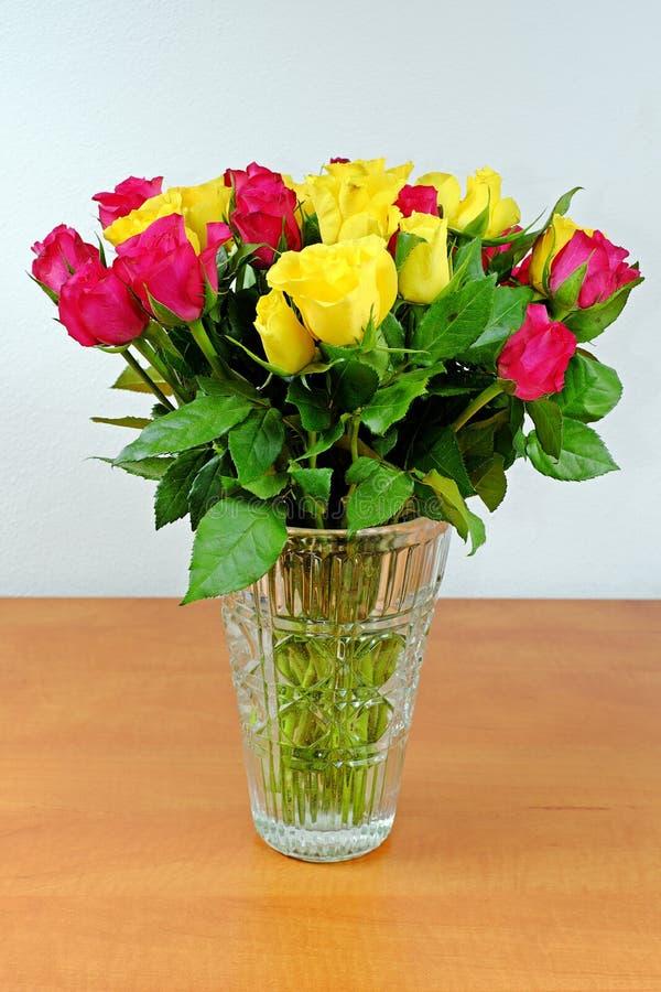 Boeket van gele en roze rozen in een glasvaas stock afbeeldingen