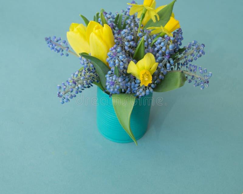 Boeket van gele narcissen, tulpen en Muscari Pasen De paaseieren zijn blauw en turkoois stock foto's
