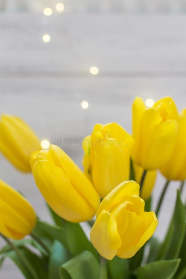 Boeket van gele tulpen en slingers op een witte houten raad stock foto
