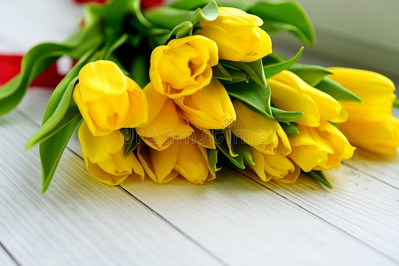 Boeket van gele tulpenbloemen op witte houten achtergrond Het wachten op de lente Gelukkige Pasen-kaart, de dag van de moeder, 8  stock foto