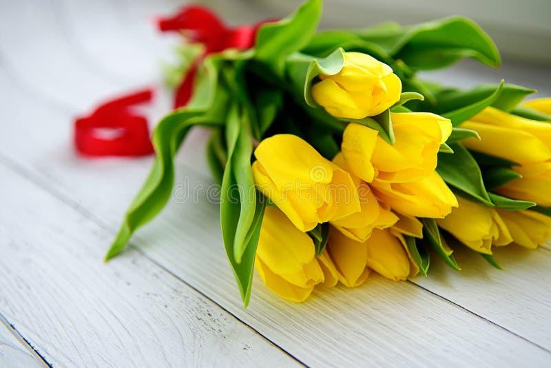 Boeket van gele tulpenbloemen op witte houten achtergrond Het wachten op de lente Gelukkige Pasen-kaart, de dag van de moeder, 8  royalty-vrije stock foto