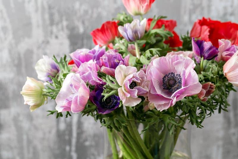 Boeket van gemengde anemonenbloemen in vaas het werk van de bloemist bij een bloemwinkel stock foto