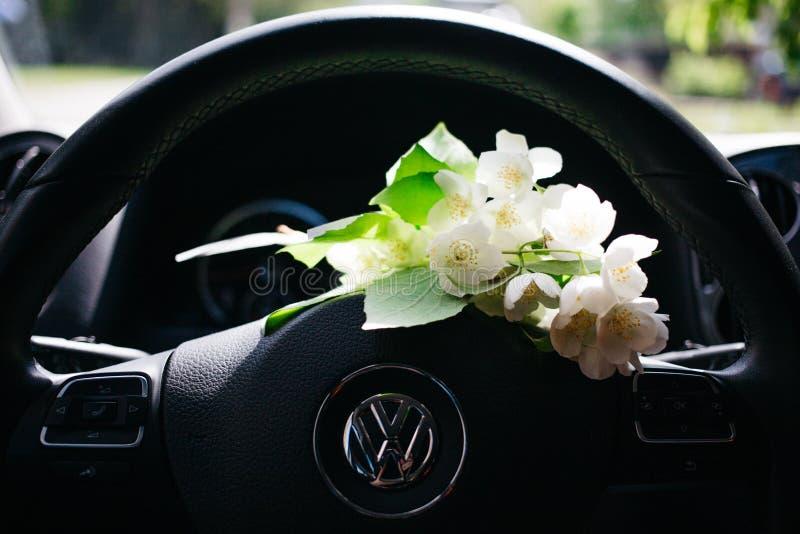 boeket van Jasmijn die op het stuurwiel van de auto liggen royalty-vrije stock fotografie