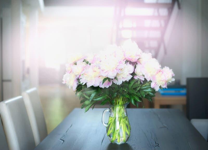 Boeket van lichtrose pastelkleurpioenen op een eettafel in de woonkamer royalty-vrije stock fotografie