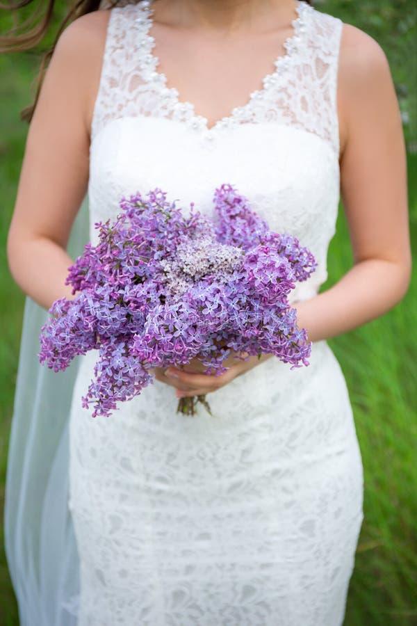 Boeket van lilac bloemen in de handen van de bruid royalty-vrije stock foto's