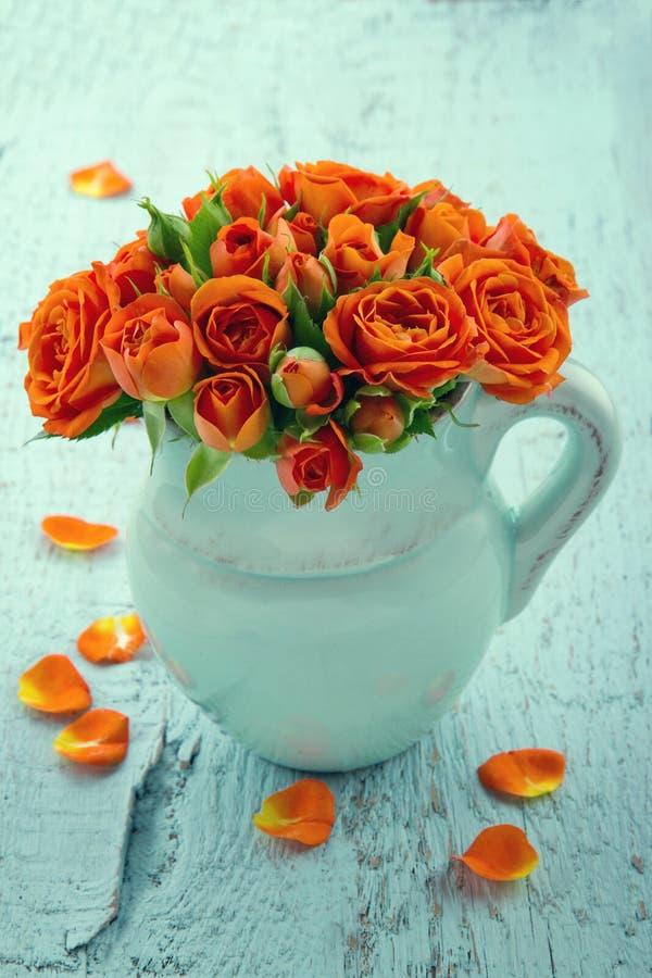 Boeket van oranje rozen in een blauwe vaas stock fotografie