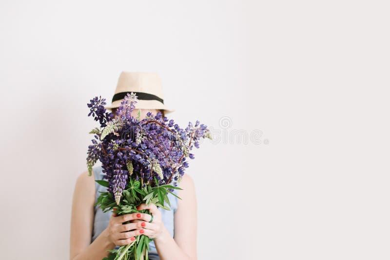 Boeket van purpere lupines in vrouwenhanden op witte achtergrond Bloemist minimaal concept De zomerbloemen van de vrouwengreep royalty-vrije stock foto