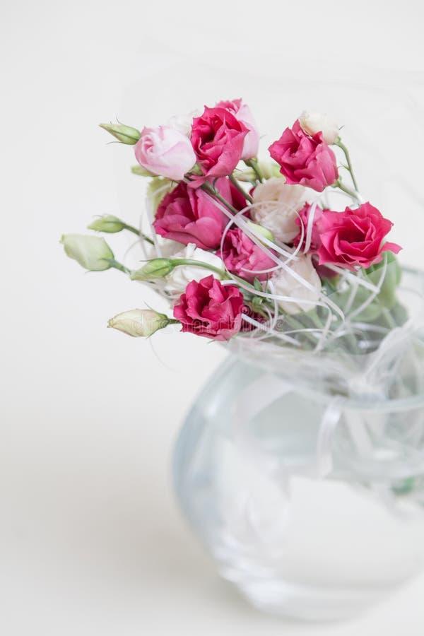 Boeket van rode Eustoma-bloemen in vaas op witte achtergrond stock foto's