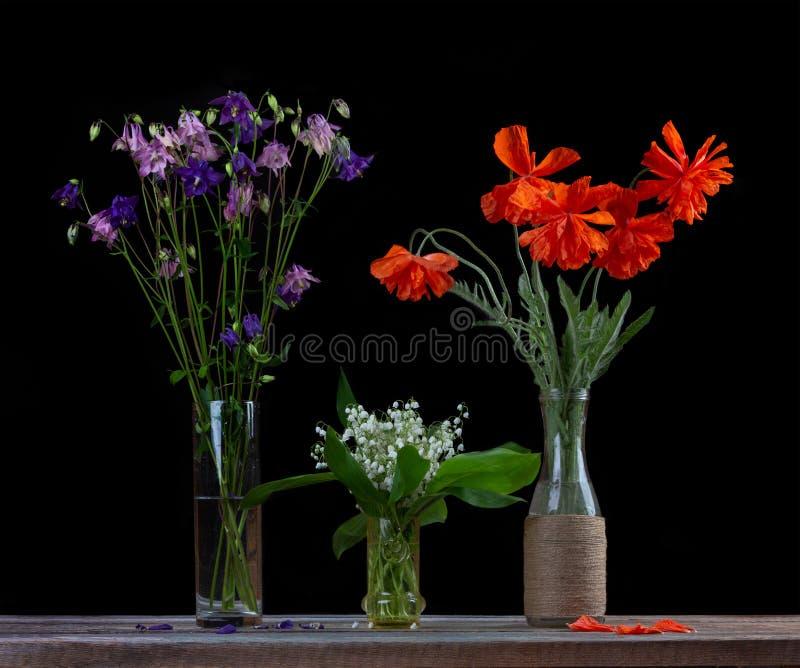 Boeket van rode papavers, een boeket van witte lelietje-van-dalen en een boeket van bloemenklokken in glasvazen op een zwarte bac stock afbeelding