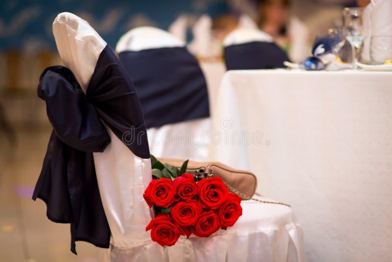Boeket van rode rozen op een stoel een gift bij het huwelijk Bloemen als gift huwelijksdecoratie van het restaurant stock afbeelding