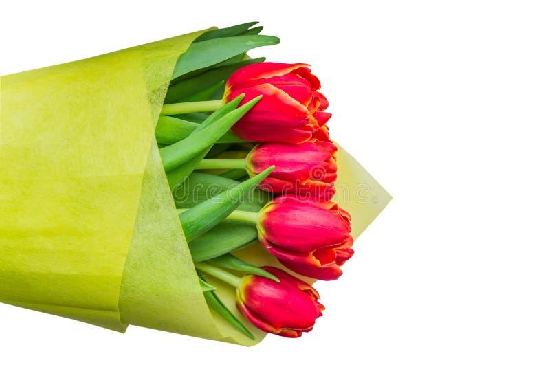 Boeket van rode tulpen in geel verpakkend die document op witte achtergrond wordt geïsoleerd stock foto