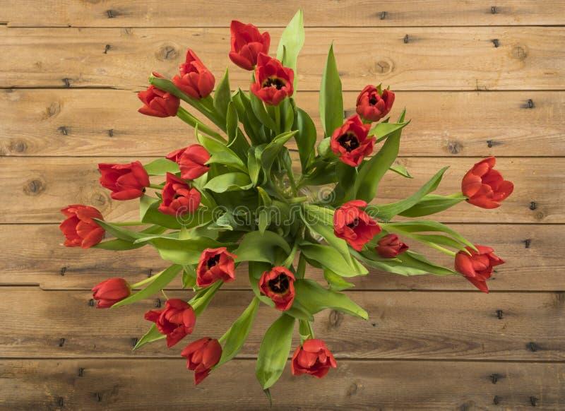 Boeket van rode tulpen in vaas op houten lijst, hoogste mening stock afbeelding