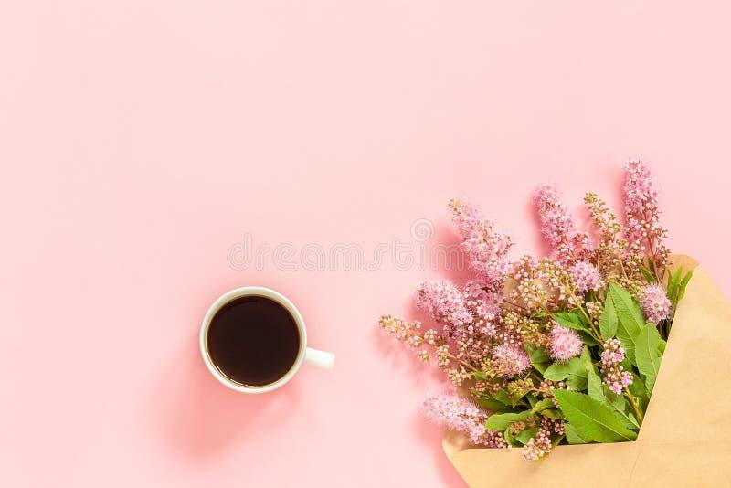 Boeket van roze bloemen in envelop, kop van koffie en een witte lege kaart voor tekst op roze achtergrondconceptengoedemorgen of stock afbeeldingen