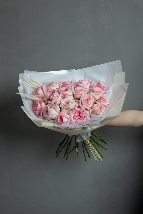 In boeket van roze rozen in de uitgestrekte hand op een grijze achtergrond royalty-vrije stock afbeeldingen