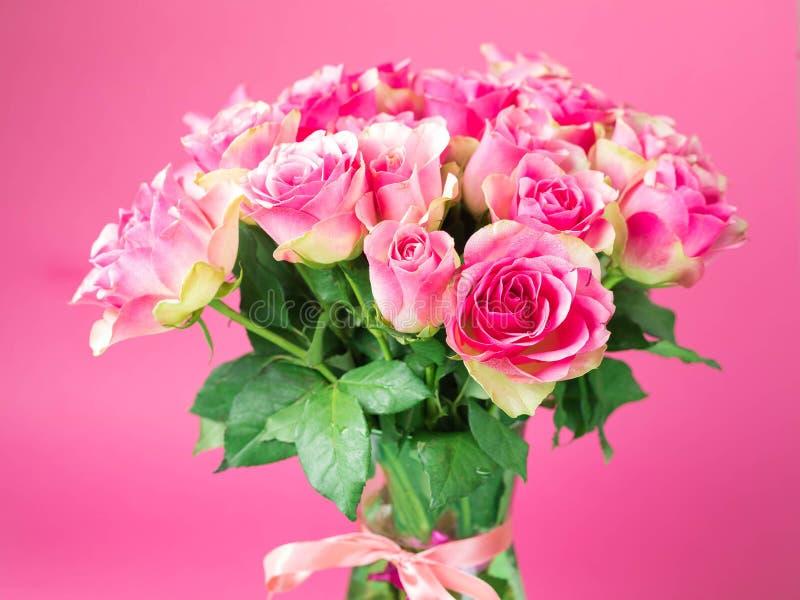 Boeket van roze rozen in een glasvaas op een roze achtergrond Op een vaas zijn de bureaucratische formaliteiten gebonden Op de ro stock afbeelding