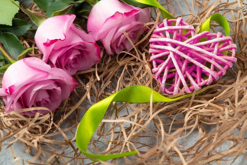 Boeket van roze rozen en een rieten hart met decoratie op lijst-concept liefde en gelukwensen voor gehouden van  royalty-vrije stock foto