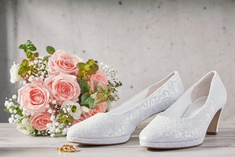 Boeket van roze rozen naast huwelijksschoenen stock foto's