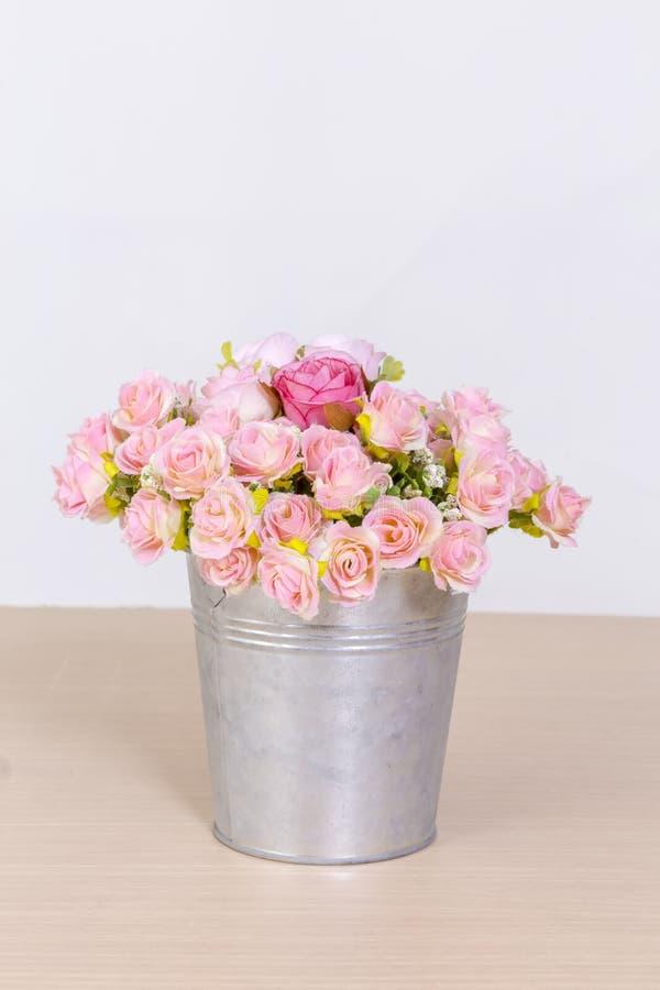 Boeket van roze rozen in uitstekende pot op houten achtergrond stock fotografie
