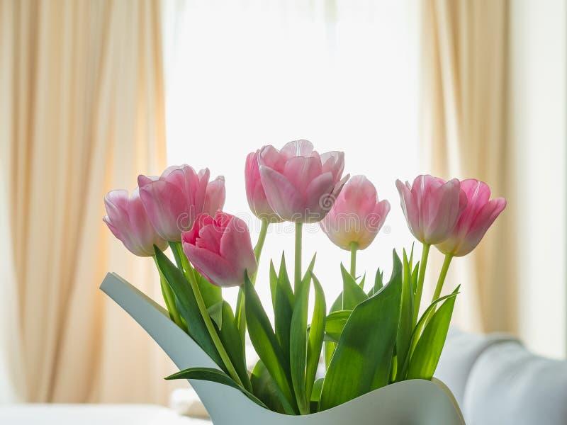 Boeket van roze tulpen in vaas in vorm van gieter tegen het venster stock fotografie
