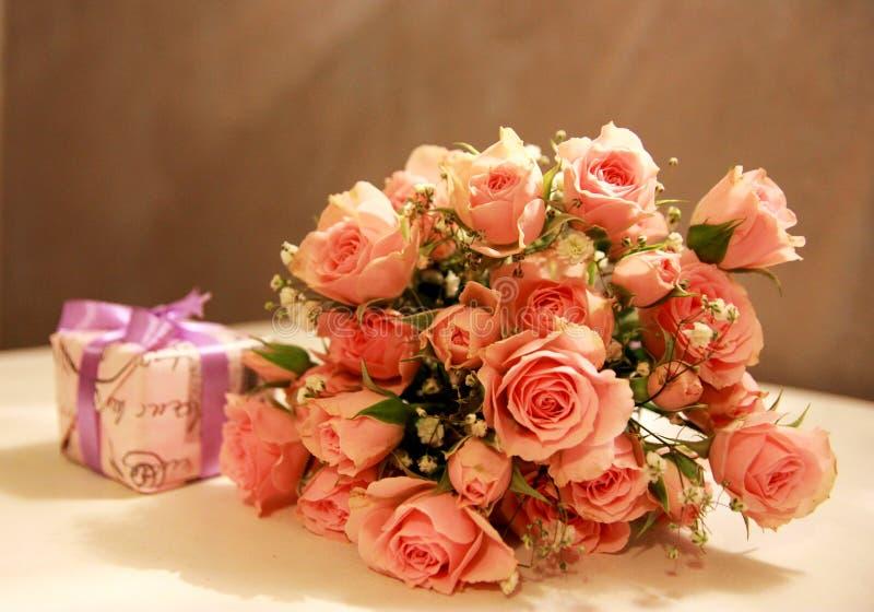 Boeket van rozen en een gift royalty-vrije stock afbeelding