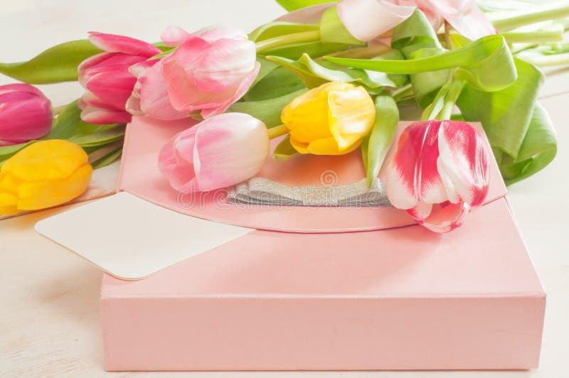 Boeket van tulpen, giftdoos en lege groetkaart stock foto's