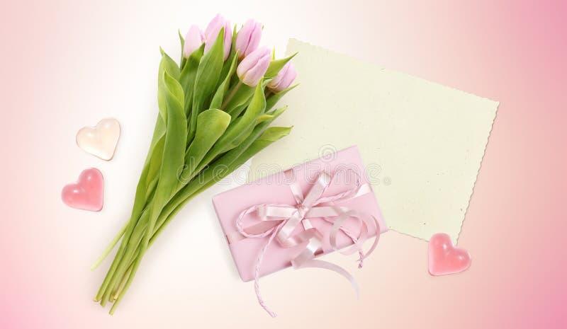 Boeket van tulpen, kaart, harten en doosgift op roze royalty-vrije stock afbeelding