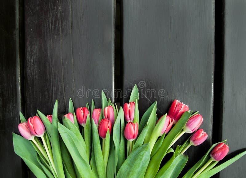 Boeket van tulpen in mand op houten achtergrond stock foto's