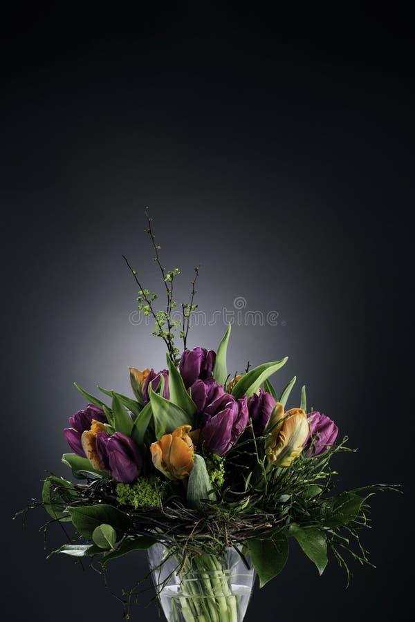 Boeket van tulpen in vaas op dark royalty-vrije stock fotografie