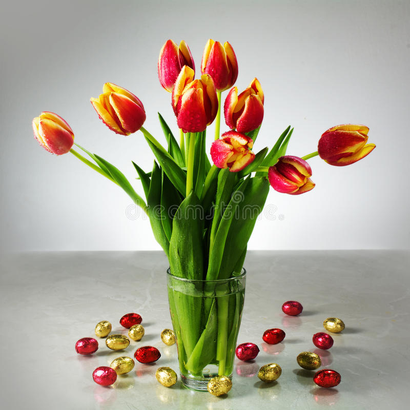 Boeket van verse tulpen en kleine rode gele chocolade Pasen b.v. royalty-vrije stock afbeeldingen