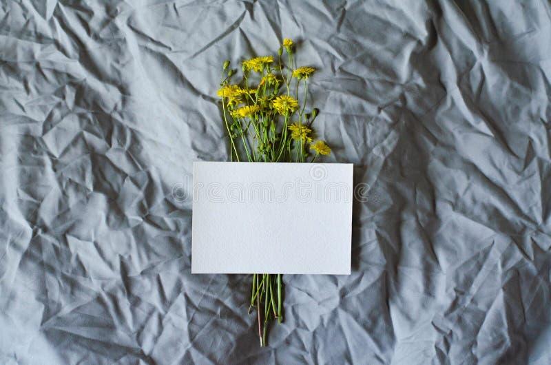 Boeket van wilde bloemen en een blad van document op een grijze stof stock foto