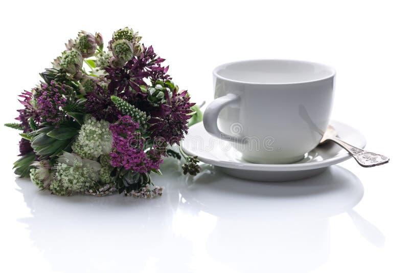 Boeket van wilde bloemen en een witte kop met een schotel op een witte achtergrond Ge?soleerdeo samenstelling stock fotografie