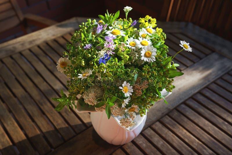 Boeket van wilde bloemen in witte vaas op houten lijst royalty-vrije stock afbeelding