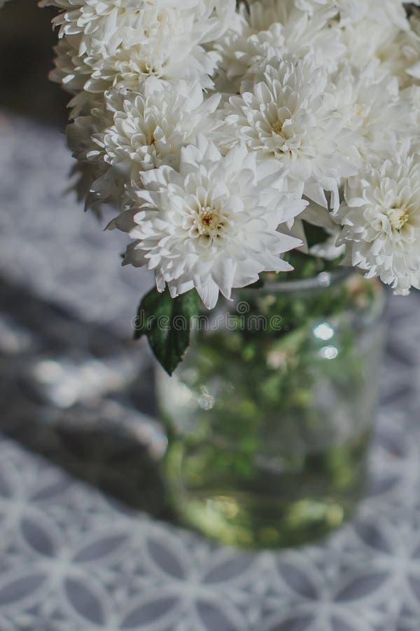 Boeket van witte chrysantenbloemen in een glasvaas stock foto's