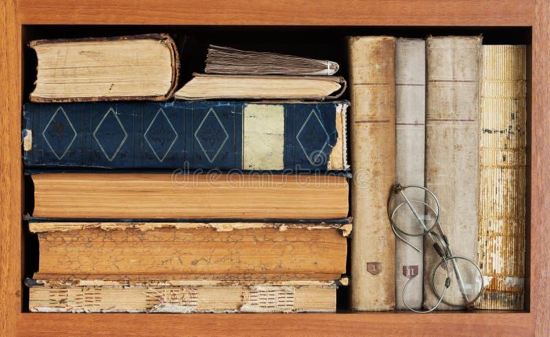 Boekhandel binnen Uitstekende boekeninzameling, antieke boek geweven dekking, oude manierbril oud houten plankenkader stock foto