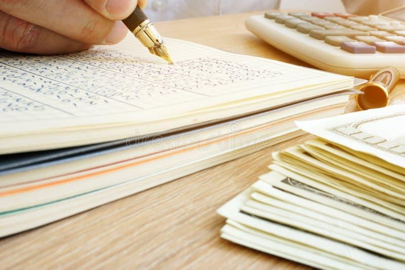 Boekhouder het schrijven bedrijfsrapport Documenten, geld en calculator royalty-vrije stock foto