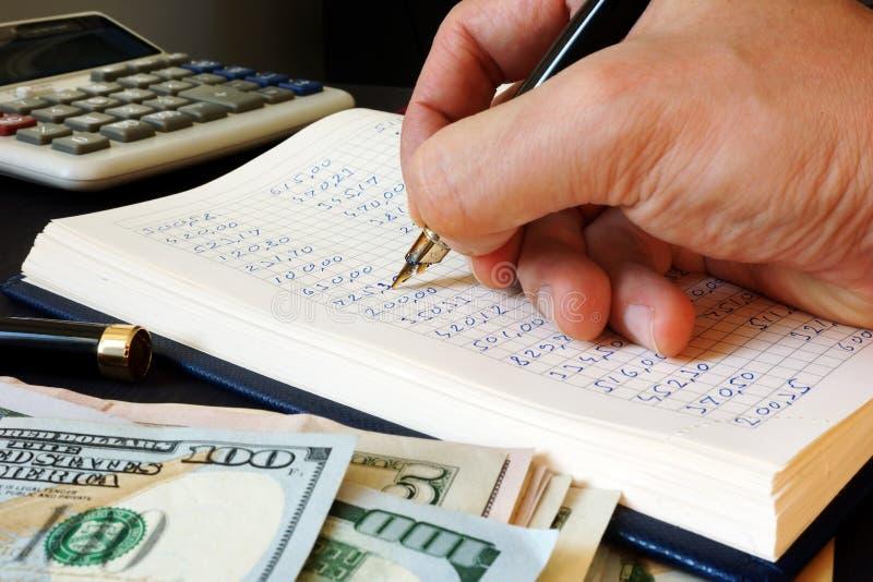 Boekhouder het schrijven financieel verslag in het boekhoudingsboek stock foto's