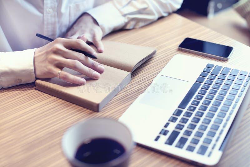 Boekhoudings het bedrijfsmens schrijven businessplan, gebruikslaptop computer en mobiele telefoon in koffie, het drinken koffie stock afbeelding