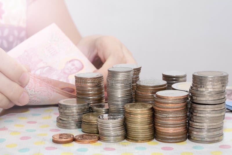 Boekhoudingsconcepten huidig door de Vrouwelijke rekeningen van hand tellende Baht achter de stapels van het geldmuntstuk op wit royalty-vrije stock afbeelding