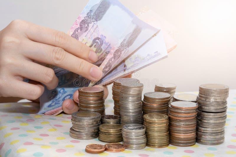 Boekhoudingsconcepten huidig door de Vrouwelijke rekeningen van hand tellende Baht achter de stapels van het geldmuntstuk op wit stock foto
