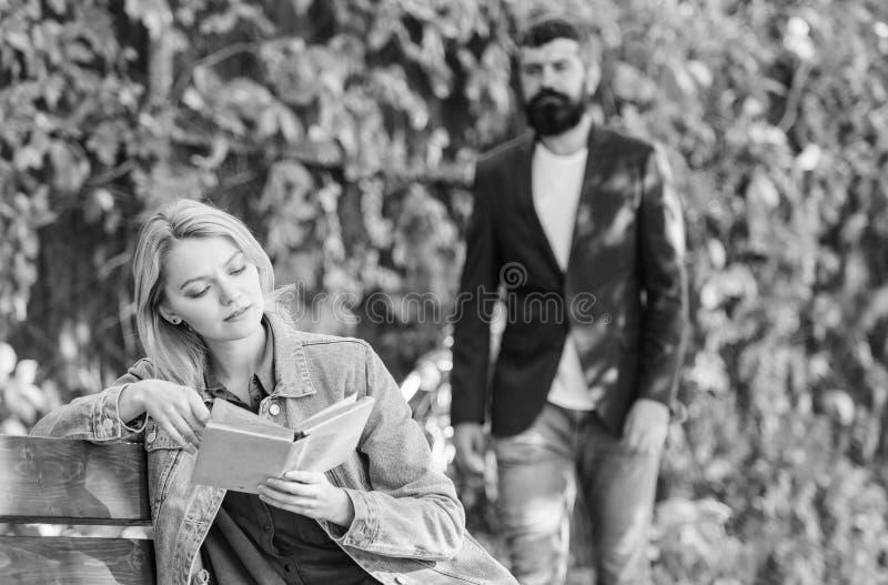 Boeklezing De stemming van de lente meisje met boek op bank gebaarde mensengang in park Verbeelding en inspiratie Diep in Liefde stock foto's