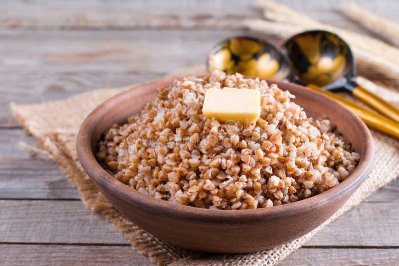 Boekweit in een kom Gezond voedsel Boekweithavermoutpap en boter royalty-vrije stock afbeelding