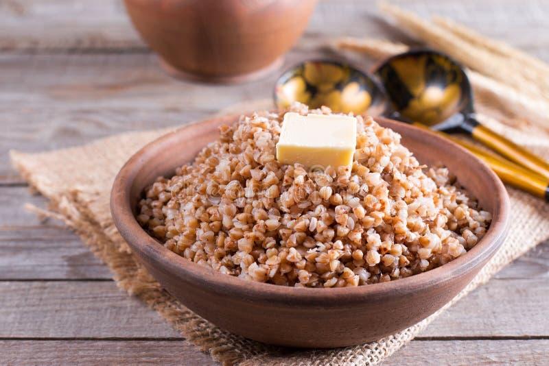 Boekweit in een kom Gezond voedsel Boekweithavermoutpap en boter stock afbeelding